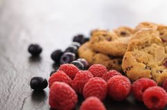 Cookies raspberries blueberries. A few homemade cookies and raspberries and blueberries on black background Royalty Free Stock Image