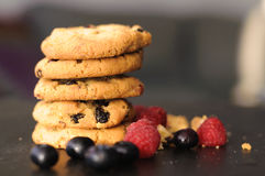 Cookies raspberries blueberries. A few homemade cookies and raspberries and blueberries on black background Stock Photography