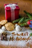 Cookies and  red package with text written in sugar. Fudge an home made cookies, and  a red gift package with text `sweet holidays` written in sugar Stock Image
