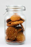 Anzac biscuits in glass jar. Home-baked Anzac biscuits preserved in an old-fashioned glass jar - isolated, neutral background Royalty Free Stock Photography