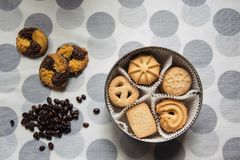 Cookies in a round box and three lying with coffee beans on a tablecloth with polka dots. Cookies with sugar in a round box and three lying with coffee beans on stock photography