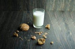 Cookies saborosos e vidro do leite no fundo de madeira Fotos de Stock Royalty Free