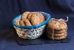 Cookies saborosos polvilhadas com as sementes de sésamo, girassol na placa do xisto foto de stock
