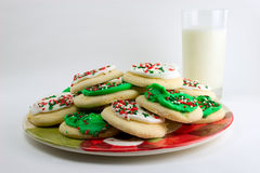 Cookies for Santa. Decorated holiday cookies on a plate with a glass of milk royalty free stock images