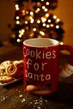 Cookies for Santa with Christmas Tree Background. Cookies for Santa mug, White plate with Danish Butter Cookies with Christmas Tree Stock Photo