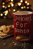 Cookies for Santa with Christmas Tree Background. Cookies for Santa mug, White plate with Danish Butter Cookies with Christmas Tree Royalty Free Stock Images
