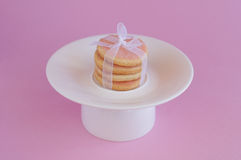 Cookies with satiny tape on pink background Stock Photos