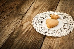 Cookies in the shape of a crown. Cookies in the shape of a heart and cookies in the shape of a crown on a white napkin on a wooden table Stock Photos