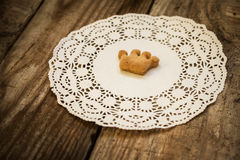 Cookies in the shape of a crown. On a white napkin on a wooden table Stock Images