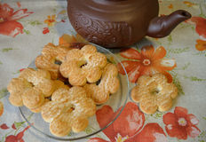 Cookies in the shape of flowers on the transparent saucer and brown clay teapot on tablecloth with orange and red flowers Royalty Free Stock Images