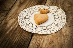 Cookies in the shape of a heart and cookies. In the shape of a crown on a white napkin on a wooden table Stock Photos