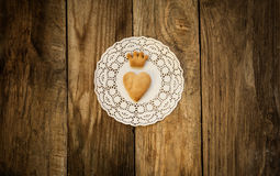 Cookies in the shape of a heart and cookies. In the shape of a crown on a white napkin on a wooden table Stock Image