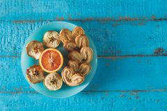 Cookies in the shape of a heart with decorative slices of dried apples on blue wooden surface. With place for text toned Royalty Free Stock Image