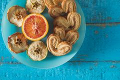 Cookies in the shape of a heart with decorative slices of dried apples on blue wooden surface. Heart shaped cookies with slices of decorative dried apples and Stock Images