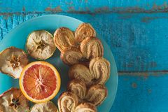 Cookies in the shape of a heart with decorative slices of dried apples on blue wooden surface. Heart shaped cookies with slices of decorative dried apples and Stock Photo