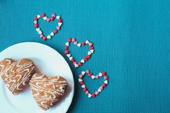 Cookies in the shape of heart on a small white plate. On a blue background stock images