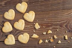 Cookies in the shape of a heart on table. Cookies in the shape of a heart whole end broken on wooden background, top view royalty free stock photo