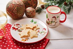 Cookies in the shape of a star on a Christmas plate and milk in a Christmas cup royalty free stock photography