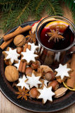 Cookies in the shape of stars, spices and mulled wine on a plate Stock Photo
