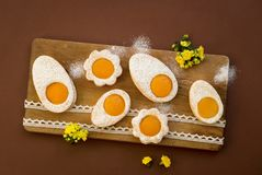 Cookies in the shape of white eggs with apricot yolk as homemade decoration. Happy Easter. Cookies in the shape of white eggs with apricot yolk as homemade royalty free stock images