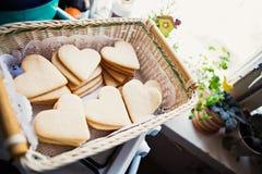 Cookies sob a forma dos corações em uma cesta de vime para o dia de Valintine Fotos de Stock Royalty Free