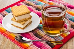 Cookies with souffle, cup with tea, spoon on napkin. Cookies with souffle in plate, transparent cup with tea, spoon on napkin on wooden table Stock Photos