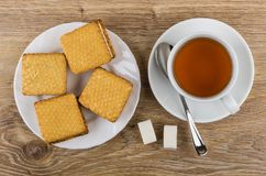 Cookies with souffle in plate, tea, spoon on saucer, sugar. Stuffed cookies with souffle in white plate, cup of tea, spoon on saucer, sugar cubes on wooden table Stock Photography