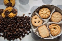 Cookies sprinkled with sugar in a round box partitioned with paper and coffee beans on a table. Cloth with dots stock images