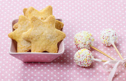 Cookies in star shape and white cake pops. Decorated with colorful sprinkles on dotted table cloth royalty free stock image