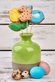 Cookies on sticks in vase. Easter eggs on wooden surface. Easter bakery ideas Stock Images