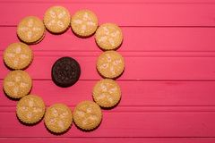 Cookies with strawberry flavor cream surrounding a black chocolate cookie stock photography