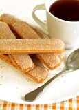 Cookies strewed by sugar and cup of tea Royalty Free Stock Image