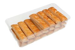 Cookies from strips of puff yeast dough with sugar glaze in plastic box isolated. Cookies from strips of puff yeast dough with sugar glaze in plastic box royalty free stock images