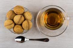 Cookies in form nut in bowl, teaspoon, tea on table. Cookies with stuffed in form nut in bowl, teaspoon, tea on wooden table. Top view Stock Image