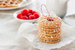 Cookies with sugar drops and red ribbon on a white plate with raspberries on a background on a linen textile Stock Image