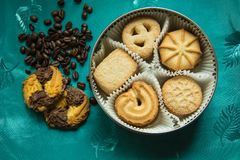 Cookies with sugar in a round box and coffee beans. Cookies with sugar in a round box and two lying on a green tablecloth with coffee beans royalty free stock photo