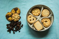Cookies with sugar in a round box and three lying on a blue tablecloth with coffee beans. Cookies with sugar in a round box and three lying on a light blue stock photos