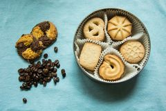 Cookies with sugar in a round box and two lying on a tablecloth with coffee beans. Cookies with sugar in a round box and two lying on a light blue tablecloth royalty free stock photo