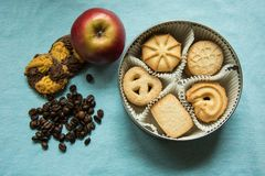 Cookies with sugar in a round box, two lying on a tablecloth with coffee beans and one apple. Cookies with sugar in a round box, two lying on a light blue stock image
