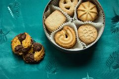 Cookies with sugar in a round box and two lying on a tablecloth. Cookies with sugar in a round box and two lying on a green tablecloth royalty free stock photography