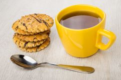 Cookies with sunflower seeds, sesame, teaspoon and cup of tea. On wooden table Stock Photography
