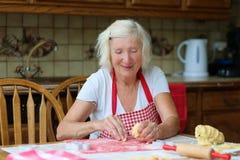 Cookies superiores felizes do cozimento da mulher na cozinha imagens de stock royalty free