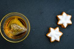 Cookies and tea. Delicious home made  christmas star cookies, a cup of tea  on black background Royalty Free Stock Photography