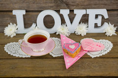 Cookies, tea, flowers and happy mothers day card with love text. On wooden plank royalty free stock images