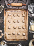 Cookies to form balls on baking tray preparation on kitchen table background with ingredients and Dough roll Stock Images