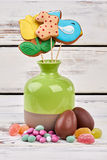 Cookies in vase and sweets. Chocolate Easter eggs on wood Royalty Free Stock Photo