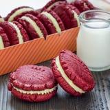 Cookies vermelhas do sanduíche de veludo com o queijo creme que enche-se na tabela de madeira, formato quadrado Fotos de Stock