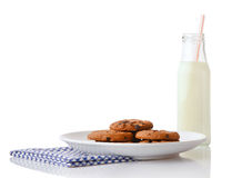 Cookies on white ceramic plate on blue napkin and bottle of milk with straw Royalty Free Stock Photography