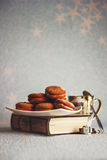 Cookies on a white plate on a old book Stock Images