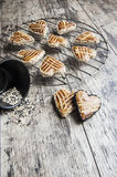 Cookies whith sesame in the shape of heart on the metal grille Stock Images